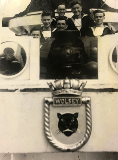 Shipmates pose with ship's crest, HMS Wolsey